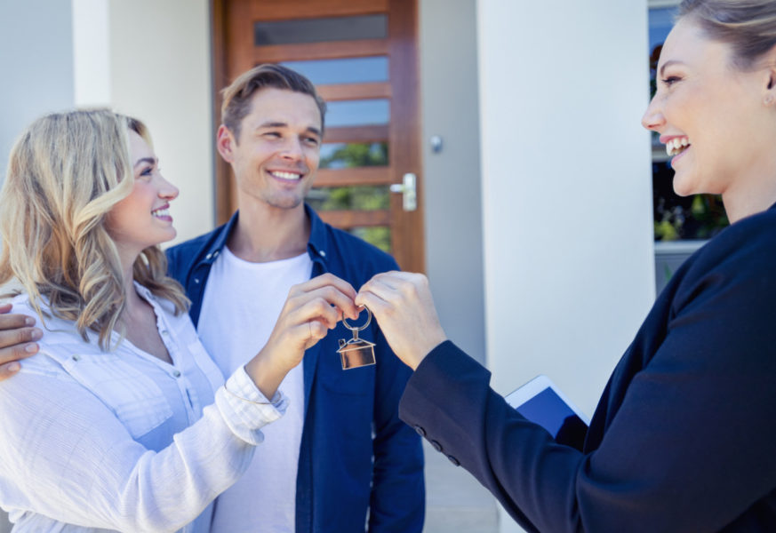 Real estate agent giving a young couple the key to their new house.